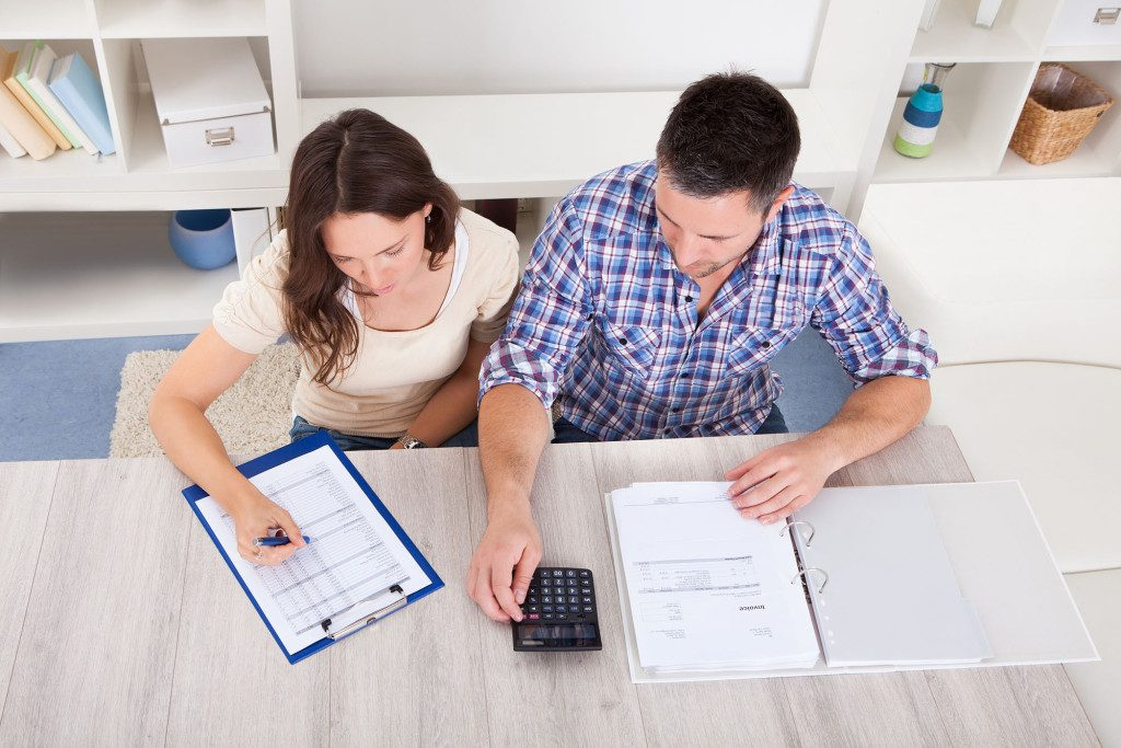 Portrait Of A Young Couple Calculating Finance At Desk